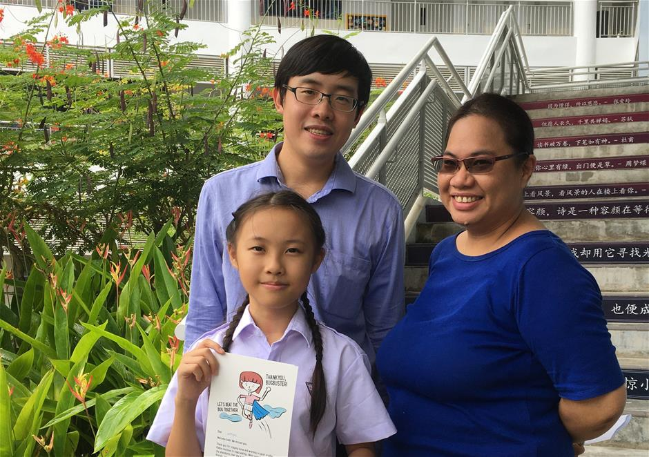 Wenyao with her Form teachers, Mr Raymond Teo and Ms Jennifer Lai. In her hands, a Thank You card from her teachers for doing her part to contain the spread of the virus.