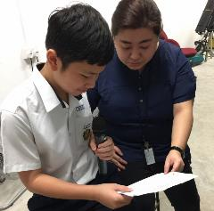 Miss Cao Yu, guiding a Secondary 2 student in delivering The Daily News @ AES